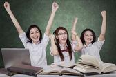 Three cheerful schoolgirls celebrate winning — Stock Photo