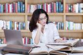 Student sitting in library while reading books — Stock Photo