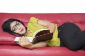 Excited woman resting on sofa while reading book — Stock Photo