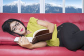 Pretty woman lying on sofa while reading book — Stock Photo