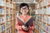Happy elementary school student reads book — Stock Photo