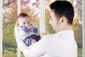 Cheerful father holds his cute baby — Stock Photo