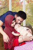 Happy muslim parents kiss their child — Stock Photo