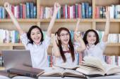 Cheerful schoolgirls raise hands together in library — Stock Photo