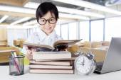 Attractive little learner reading books in class — Stock Photo