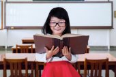 Child standing in class while reading a book — Stock Photo