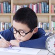 Little boy drawing in library with a clock on desk — Stock Photo #80222400