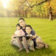 Happy children and father sitting at autumn park — Stock Photo #80734582