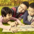 Two kids and dad reading a book while lying at park — Stock Photo #80735538