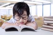 Little student enjoy read books in class — Stock Photo