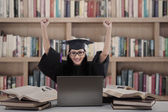 Successful female graduate with laptop at library — Stock Photo