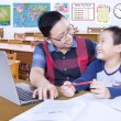 Teacher guiding male student in the classroom — Stock Photo #81405440