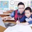 Young teacher guides his student to learn — Stock Photo #81405608