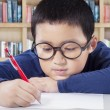 Student writing on the paper in the library — Stock Photo #81405284