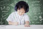 Child learning in class while wearing headphones — Fotografia Stock