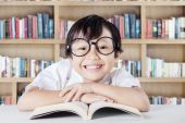 Child showing a toothy smile in the library — Stock Photo