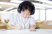 Child wearing earphones in listening lesson — Stock Photo