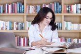 Clever high school student writing in the library — Stockfoto