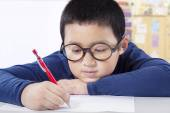 Cute boy writing on the paper in class — Stock Photo