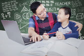 Male student talking with teacher while studying — Stock Photo