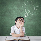 Primary school student imagining a light bulb — Stock Photo
