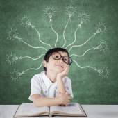 Primary school student with branchy light bulb — Stock Photo