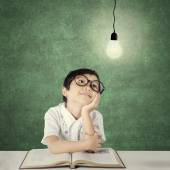 Smart primary school student looking at light bulb — Stock Photo