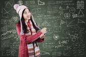 Student in sweater writes on lipboard at class — Stock Photo