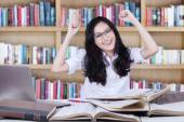 Teenage girl expressing happy in the library — Stock Photo
