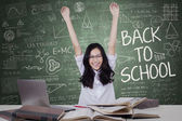 Teenage girl raising hands in the class — Stock Photo
