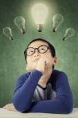 Thoughtful male student under light bulb — Stock Photo