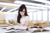 Female learner writing on the book in class — Stock Photo