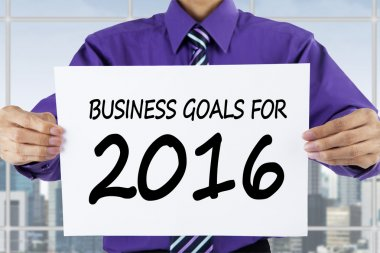 Worker showing business goals for 2016 in office