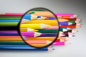 Colored pencils under loop - careful choice of color — Stock Photo