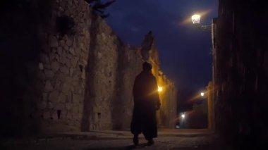 Woman walking alone on illuminated alley — Stock Video
