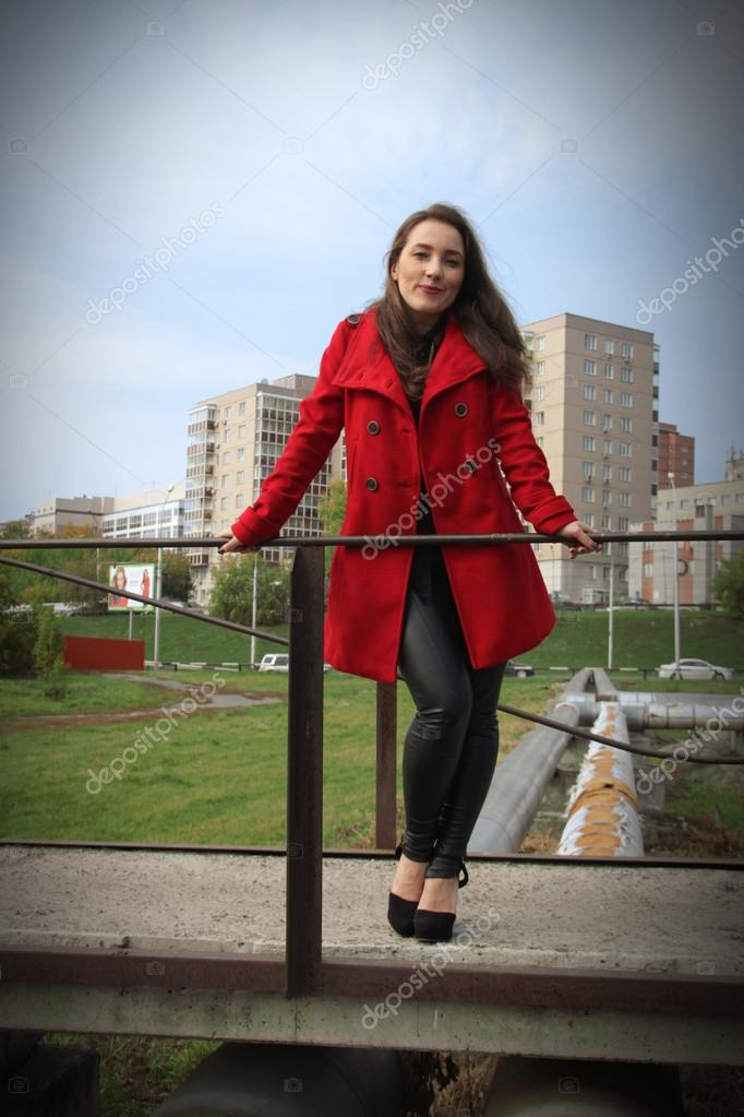 Beautiful girl in a red coat holding on to the railing on bridge