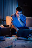Businessman working overtime at home until late — Stock Photo