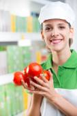 Sales clerk with fresh tomatoes — Stock Photo