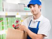 Sales clerk with cardboard box — Stock Photo