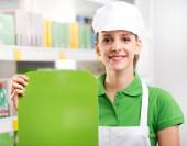 Female sales clerk with green sign — Stock Photo