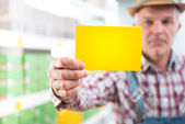 Farmer with sign at supermarket — Stock Photo