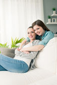 Girlfriends hugging on sofa — Stock Photo