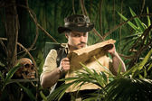 Lost explorer examining a map — Stock fotografie