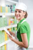 Female sales clerk with tablet at supermarket — Stock Photo