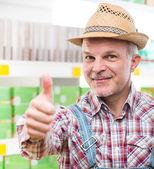 Farmer at supermarket thumbs up — Stock Photo