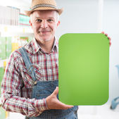 Farmer holding sign at supermarket — Stock Photo