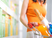 Woman at supermarket with trolley — Stock Photo