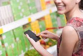 Woman with mobile at supermarket — Stock Photo