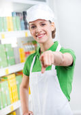 Sales clerk smiling and pointing at camera — Stock Photo