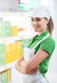 Smiling supermarket worker with shelf on background — Stock Photo